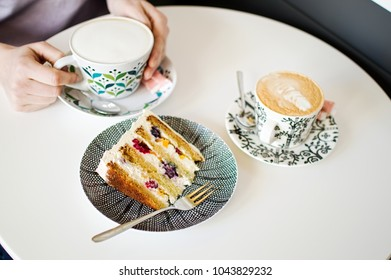 Cups of coffee with piece of cake on a table