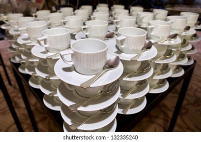 Cups for coffee and tea are seen at a table in restaurant
