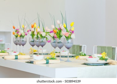 Cups with flowers on a white table