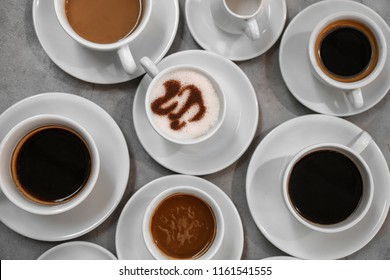 Cups of fresh aromatic coffee on grey background, top view