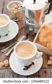 Cups of fresh coffee with brown sugar cubes and croissants