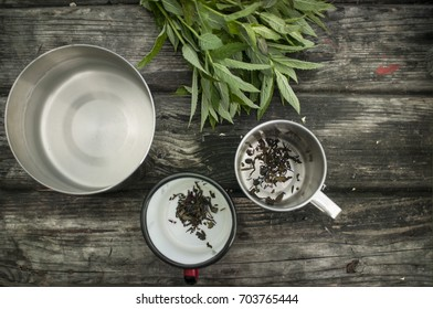Cups of herbal mint tea and bunch of peppermint on the rustic wooden background.