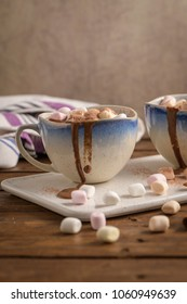 Cups of hot chocolate drink with marshmallows and cinnamon on brown wooden background.