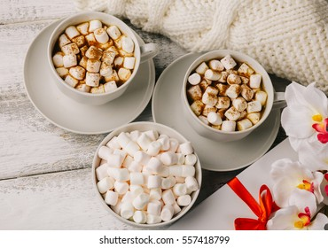 Cups with hot coffee or cocoa and marshmallows, gift box with red ribbon, white knitted blanked and flowers on white rustic wood table. Top view. Valentines day concept. Cozy winter. Toned image.