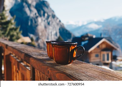 Cups of hot coffee or tea standing outdoor in winter morning. Swiss Alps