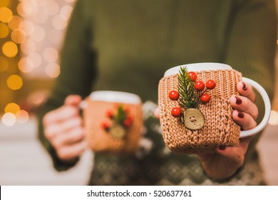 Cups of hot tea or coffee or cocoa  in knitted vintage cup holders with christmas decorations in hands of woman with beautiful festive red manicure. Woman proposing one cup into camera.