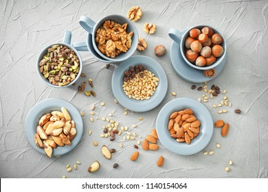 Cups and plates with different nuts on textured background