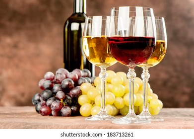 cups of red and white wine in front of grape and bottle