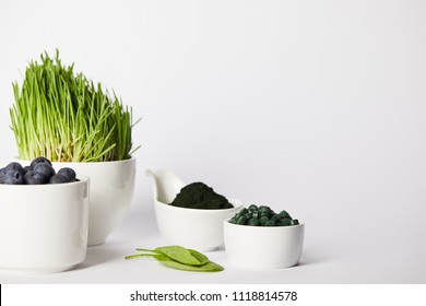 cups with spirulina grass and blueberries, leaves, bowls with spirulina powder and spirulina pills on grey background
