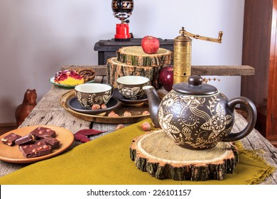 cups of tea on old wooden table, with apples, nuts, cubes of chocolate and tea pot next to them in autumn decoration