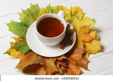 Cups of tee and autumn fall leaves on white wood still life.