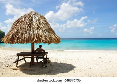 Curacao – Caribbean beach – Man relaxing on shadow – blue sea – Kenepa Chiki beach