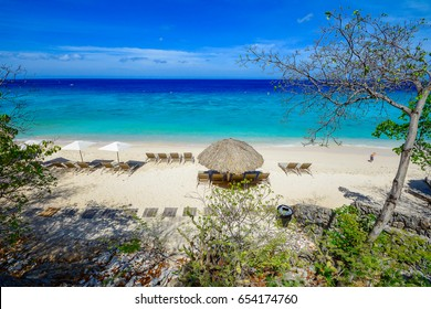 Curacao caribbean paradise beach island, relax with chairs and sofa on white sand beach with turquoise water and horizon. Visit beautiful places in the world and enjoy traveling to unique sights.