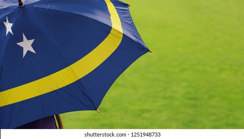 Curaçao Curacao flag umbrella. Close up of printed umbrella over green grass lawn background. Rainy weather forecast. Climate change and global warming concept.
