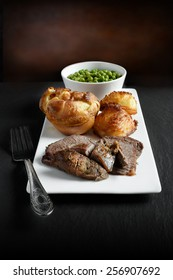 A curated image of topside roast beef, roast potatoes and traditional Yorkshire pudding in a gourmet setting against a dark background with copy space. Concept image for a Sunday lunch menu design.