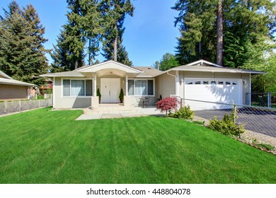 Curb appeal of beige house with well kept lawn and garage with driveway