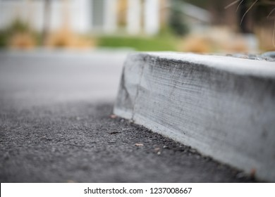 A curb with an asphalt road and a rock garden on the sides