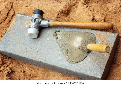 The curb hammer and spatula are on the curb