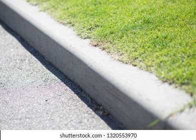 Curb near the green lawn. Green trimmed grass on the lawn. Green Grass Grows Near Black Asphalt, Separated By Concrete Border. Road And Lawn Divided By Concrete Curb. Copy space