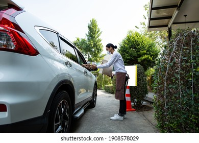 Curbside pick up.Store worker prepare and hold foods from customer order online delivery to customer in the outside.Social distance and contactless prevent covid-19.