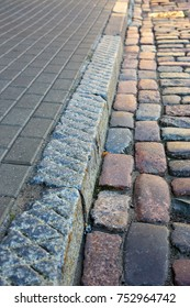 curbstone separating the pavement and the road