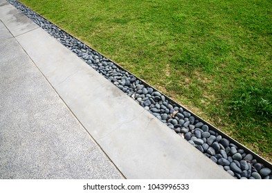 Curbstones between road and grass field
