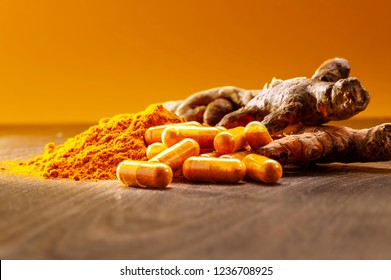 curcuma powder, curcuma capsules and curcuma roots on woodCurcuma healing power of nature