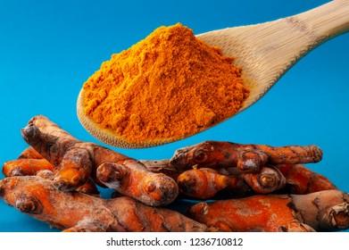 curcuma powder on a wooden spoon against blue background over curcuma roots. Curcuma healing power of nature