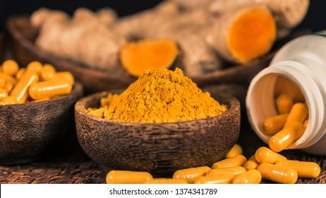 Curcumin supplement capsules, turmeric powder in glass bowl and curcuma root in background. Herbal medicine Curcuma against inflammation