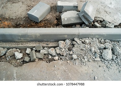 Curdstones lying on the sidewalk near the pit for installing a border. Broken asphalt surface on other side of curb. A hole in the road surface. Repair of road work