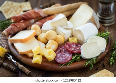 Cured meat and cheese platter or tapas tray with salami, prosciutto camembert or brie, taleggio, caprino, smoked provola balls and cubes of emmental accompanied with breadsticks and crackers