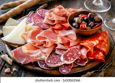 Cured meat platter with cheese and spicy olives served as traditional Spanish tapas on a wooden board. Selection of ham, salami and goat cheese