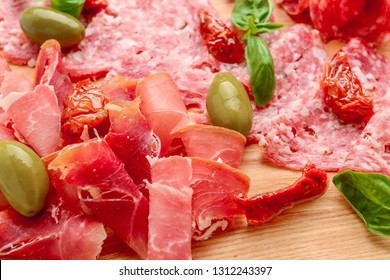 Cured meat platter of traditional Spanish tapas - chorizo, salsichon, jamon serrano, lomo - erved on wooden board with olives