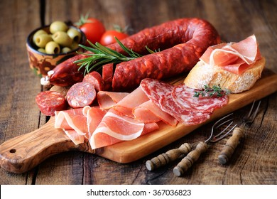Cured meat platter of traditional Spanish tapas - chorizo, salsichon, jamon serrano, lomo - erved on wooden board with olives and bread