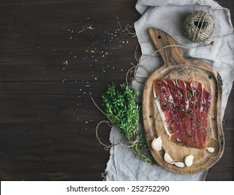 Cured pork meat prosciutto on a rustic wooden board with garlic, spices and thyme over a piece of linen fabric and dark wood background with a copy space. Top view