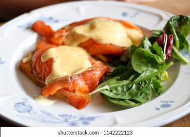 Cured Salmon Benedict with Hollandaise Sauce and Mixed Green Salad on a Plate