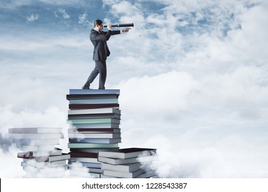 Curios businessman standing on book pile on cloudy sky and city background. Vision and education concept