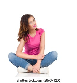 Curios Female Student. Cheerful young woman in pink shirt and jeans sitting on a floor with legs crossed and looking away. Full length studio shot isolated on white.