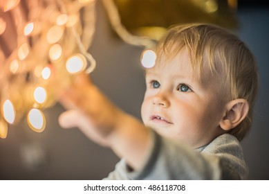 Curiosity, delight, wonder and joy on face - baby boy look in camera and smiling. He is so happy and explores christmas lightning.