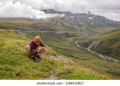 A curious and active red headed teenage boy inspects an interesting find on the Arctic tundra above high above Chandler Shelf and the Dalton highway. Alaska.