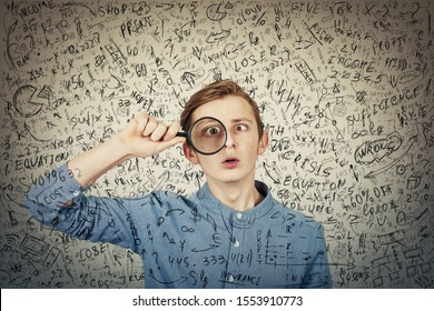 Curious, addicted boy seeking for correct answer as looks through the magnifying glass to find the response to question. Crazy student try to solve hard mathematics formula, calculation and equations.