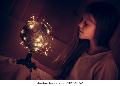 Curious admiring child girl with book in bed looking at shining night earth globe concept curiosity knowledge education development