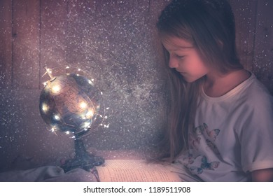 Curious admiring kid  girl with book in bed dreaming about space and universe concept astronomy curiosity knowledge education development