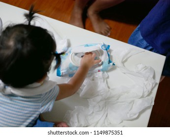 Curious Asian baby girl's hand pulling out baby wipes all over the table - messy play contributes to development of a child's physical, cognitive, sensory and creative abilities
