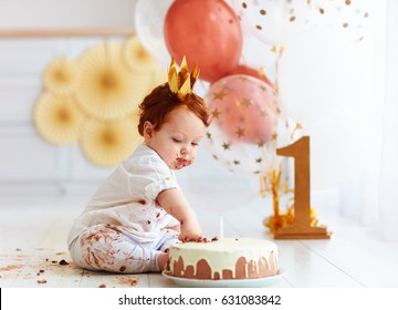curious baby boy poking finger in his first birthday cake