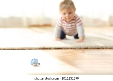 Curious baby crawling towards a dirty pacifier on the floor at home