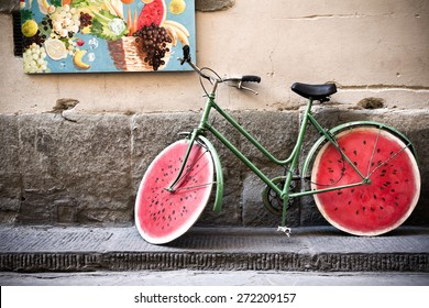 Curious bicycle placed in front of a greengrocer's shop. Wooden watermelon shaped wheels