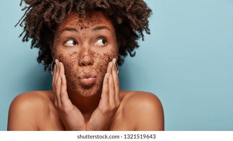 Curieuse femme noire concentrée à l'écart a le maquillage au café sur le visage applique un masque sur le visage, concentrée à l'écart, a des épaules nues, isolée sur fond bleu avec place blanche pour la promotion. Soins du corps. Cosmetology