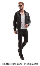 curious blonde fashion man stepping on white background and looking to side, full length picture