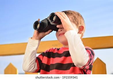 Curious boy with binoculars on a balcony